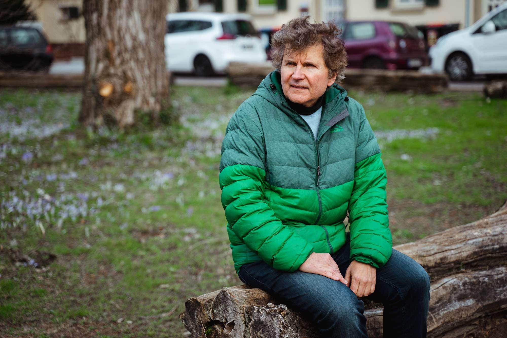 Richard Oliver Schulz sitzt auf einem Baumstmm